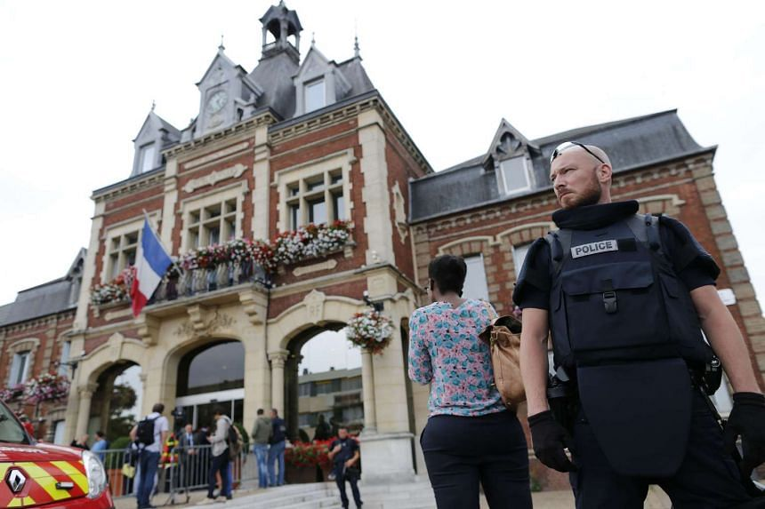 A French police officer stands guard by Saint-Etienne-du-Rouvray's city hall following a hostage-taking at a church on July 26, 2016.