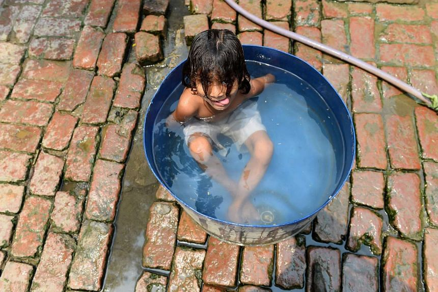 An Indian child taking a bath in Gangnauli village in Uttar Pradesh on May 8, 2016.