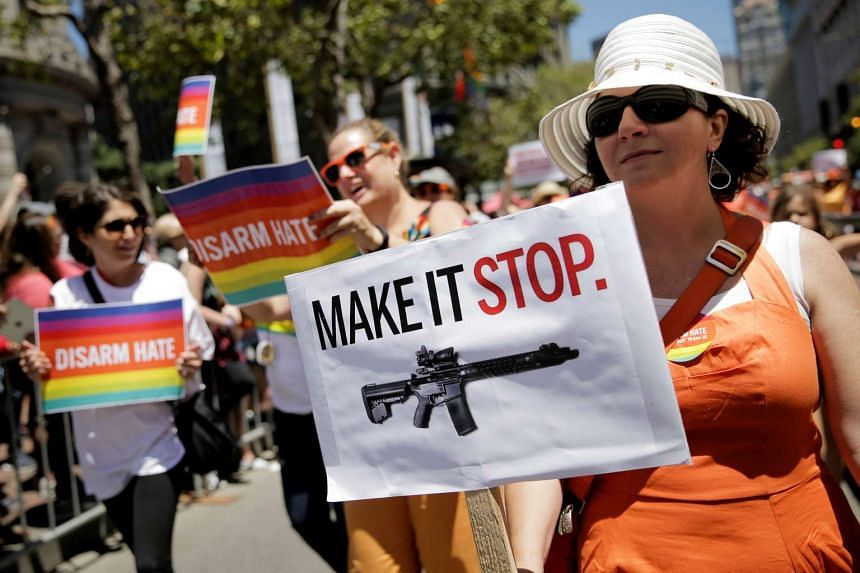 A woman holds a sign advocating for gun control in San Francisco, California, on June 26, 2016.