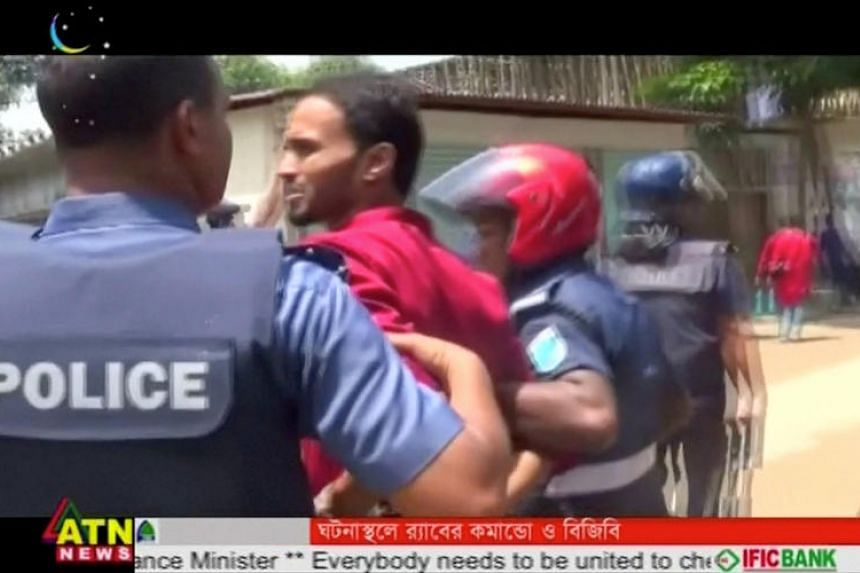 Police lead a suspect away after militants attacked Bangladeshi police guarding an Eid festival in Kishoreganj town in this still frame taken from a video on July 7.