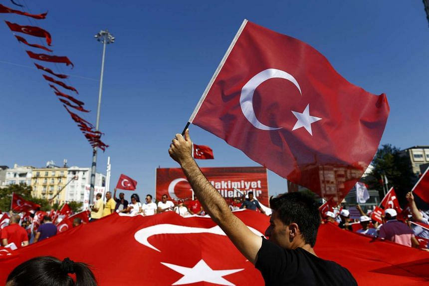 A man waves Turkey's national flag as supporters of various political parties gather in Istanbul for an opposition-organised rally, July 24, 2016.
