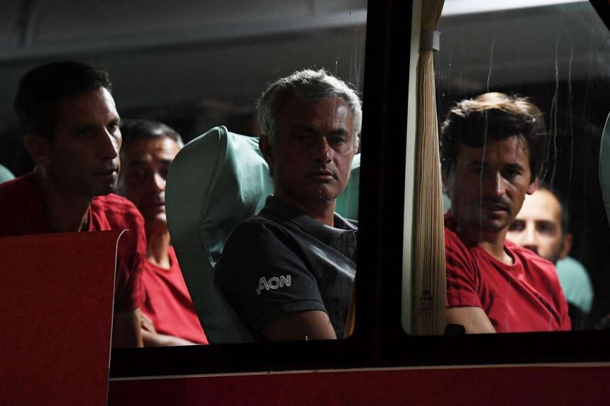 Manchester United coach Jose Mourinho (centre) looks out from the team bus before departing for the airport after the match between Manchester United and Manchester City was cancelled.