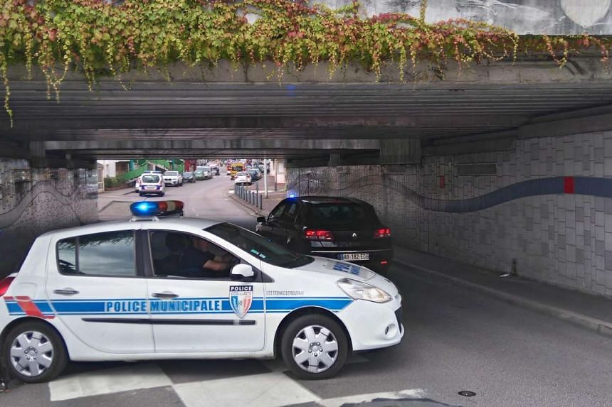 A police car blocks an underpass leading to the scene of a hostage situation in Saint-Etienne-du-Rouvray, near Rouen, France, on July 26, 2016.