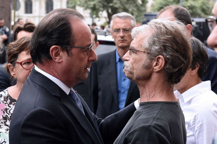 French President Francois Hollande (left) holds and speaks with Hubert Wulfranc mayor of Saint-Etienne-du-Rouvray.