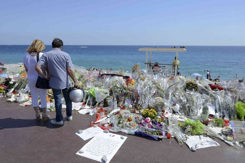 People stop near flowers left in tribute at a makeshift memorial to the victims of the Bastille Day truck attack, in Nice, on July 21, 2016.