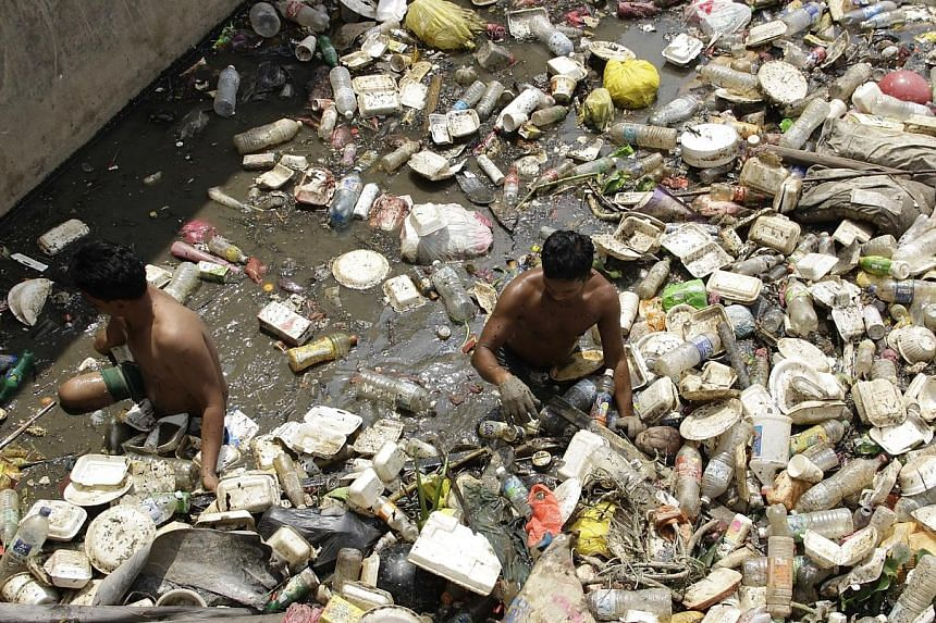 Workers clearing the trash trapped in a part of Batu River in Selangor.