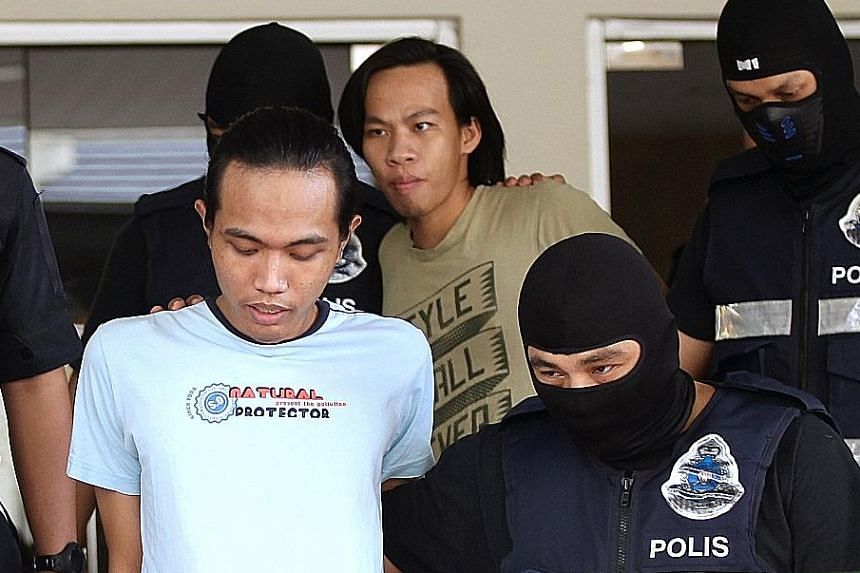Wahyudin (front) and Jonius being escorted away at the Petaling Jaya Magistrate's Court yesterday.