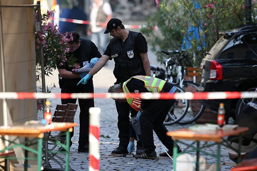 Police officers at the scene of Sunday night's suicide bombing in Ansbach, Germany, yesterday. The attacker wounded 15 people when he set off the bomb in his rucksack outside a music festival, killing himself.