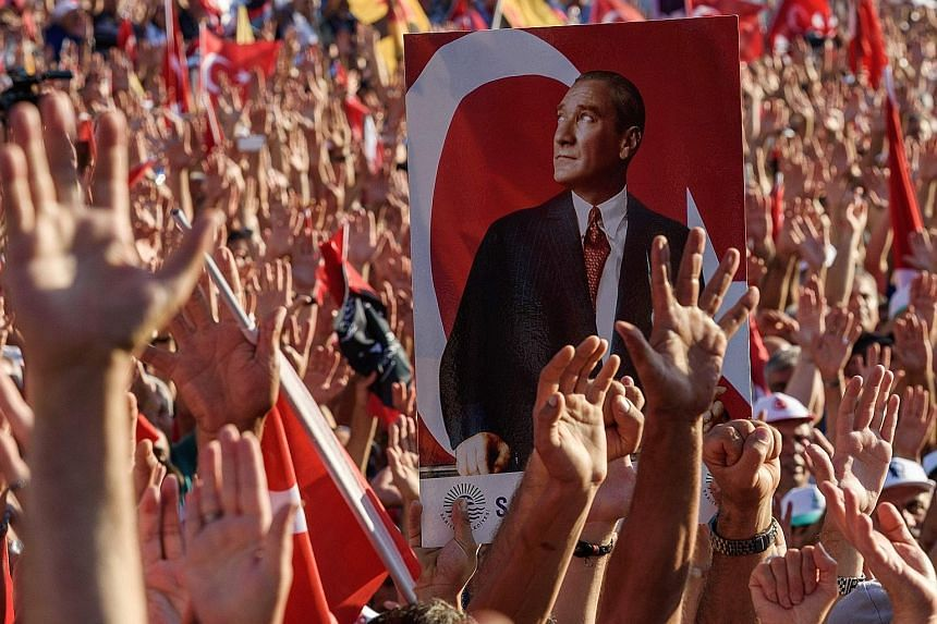 Demonstrators gathering around a picture of Mustafa Kemal Ataturk, founder of modern Turkey, during an anti-coup rally on Sunday organised by Turkey's largest opposition group, the Republican People's Party.