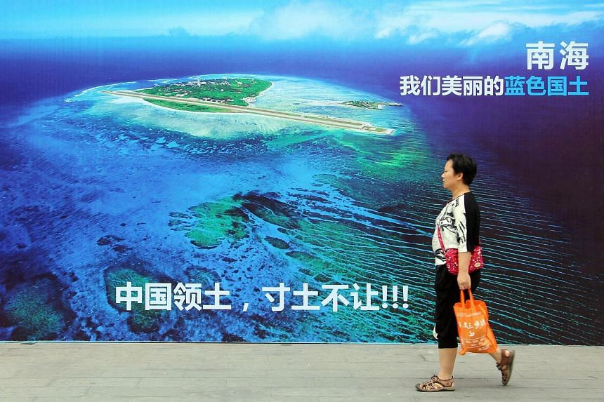 A woman walking past a poster of the South China Sea in Weifang, east China's Shandong province.