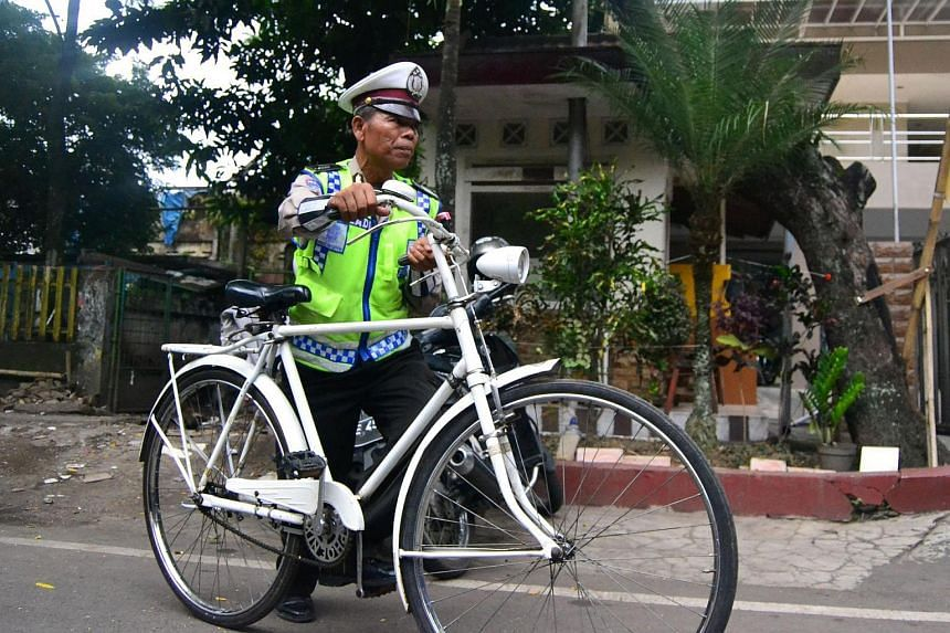 Indonesian policeman Seladi cycling to his office in Malang, East Java. Seladi, a member of Indonesia's notoriously corrupt police is to be honoured for refusing to accept bribes during his 40-year career.