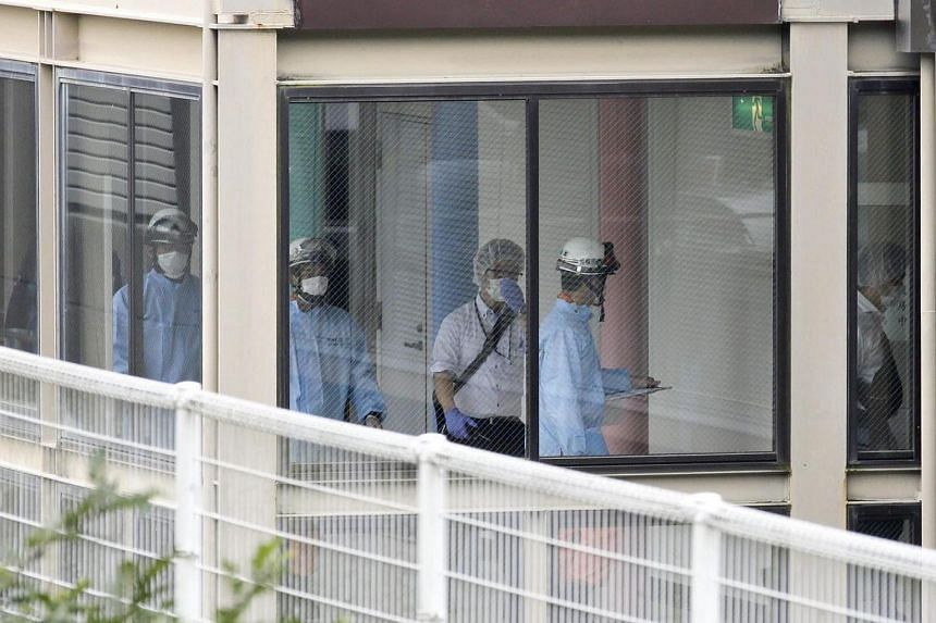 Japanese fire department medics and police officers inside Tsukui Yamayuri-en, a residential care facility for disabled people in Sagamihara on July 26.