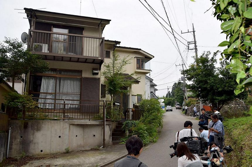 Photographers gather outside the residence of a man who went on a rampage with a knife at the Tsukui Yamayuri En care centre in Sagamihara on July 26.