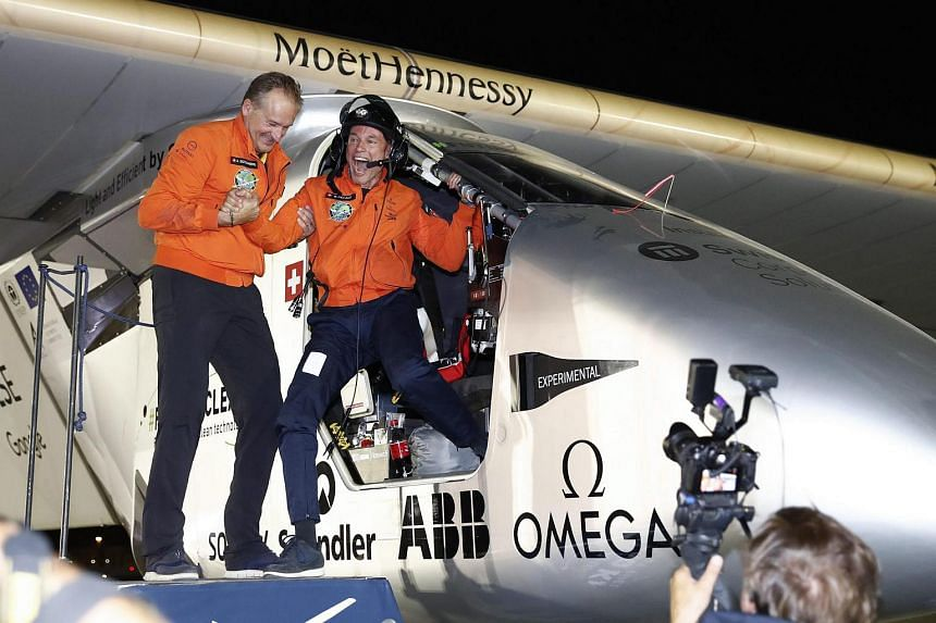 Swiss Pilot Bertrand Piccard (right) steps out of the Solar Impulse 2 aircraft next to fellow pilot and co-founder of the Solar Impulse 2 project Andre Borschberg after landing in Abu Dhabi, United Arab Emirates.