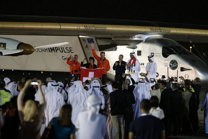 Solar Impulse 2, the solar powered plane, and crew are greeted upon arrival at Al Batin Airport in Abu Dabi to complete its world tour flight on July 26, in the United Arab Emirates.