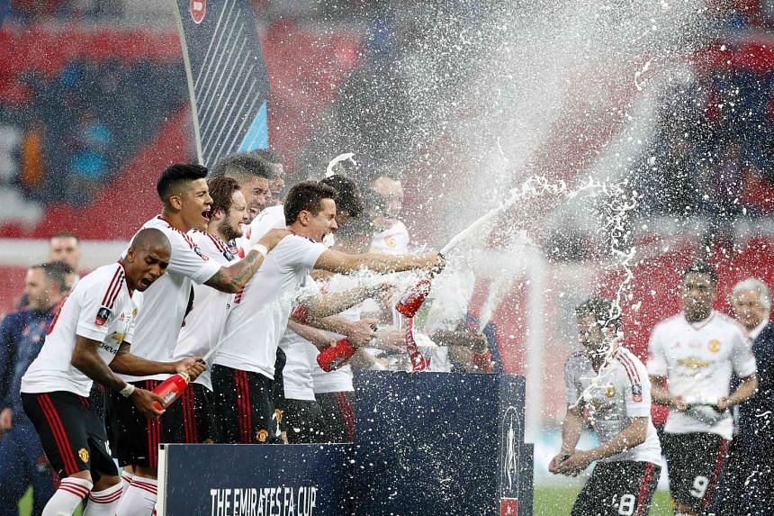 Manchester United players celebrate with the trophy after winning their English FA Cup final football match against Crystal Palace at Wembley stadium in London on May 21, 2016.