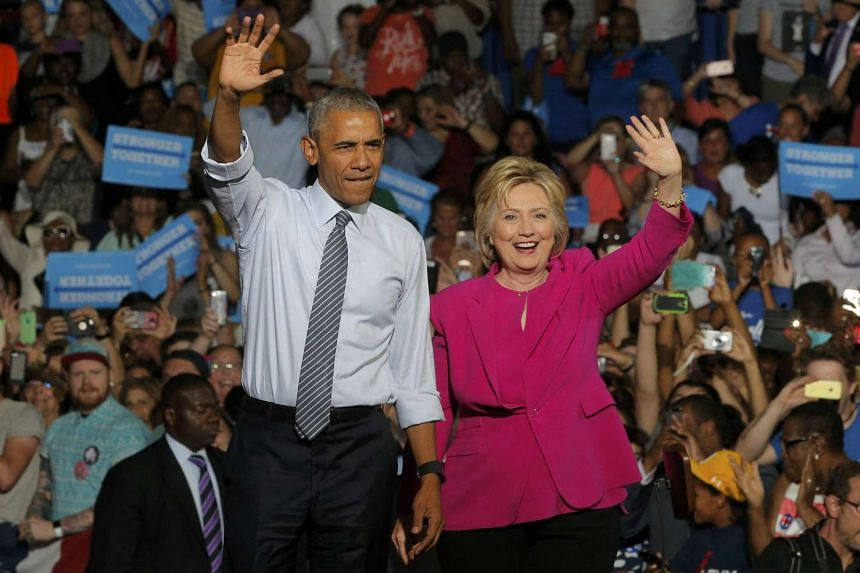 US President Barack Obama stands with presidential candidate Hillary Clinton during a Clinton campaign event in Charlotte, North Carolina on July 5, 2016.