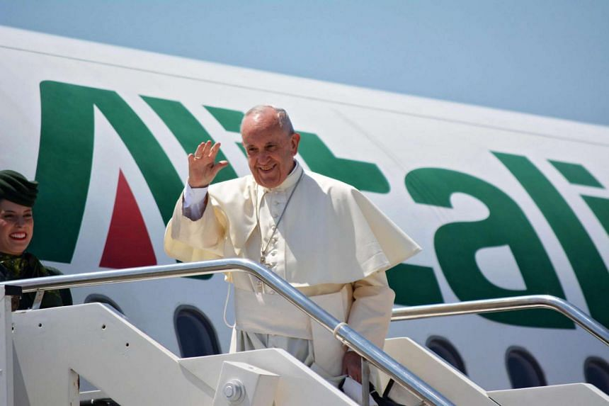 Pope Francis waves as he boards a plane for the World Youth Day 2016 in Krakow, Poland, from Fiumicino Airport in Rome on July 27, 2016.