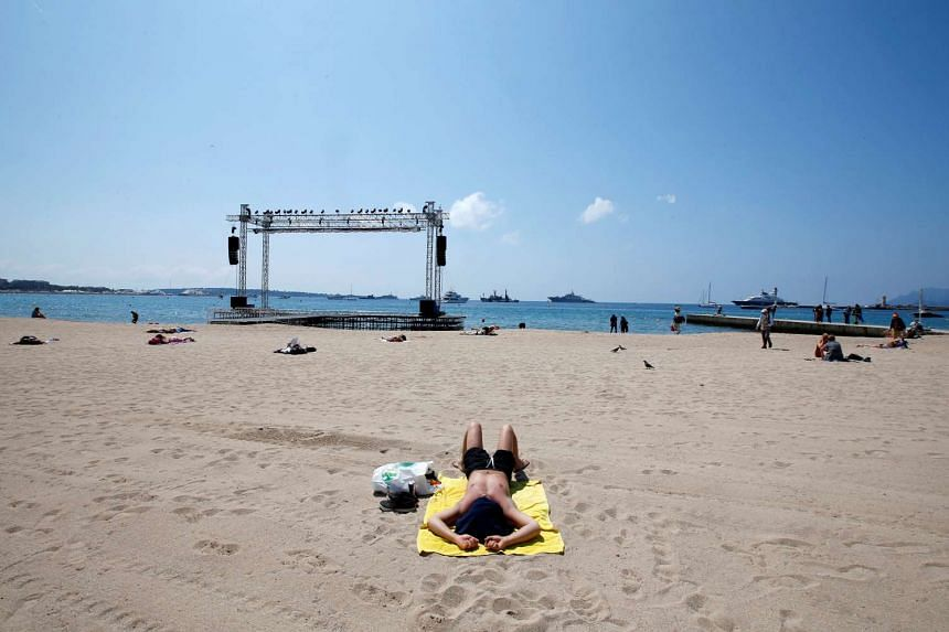 A man sunbathing on a beach in Cannes on May 17, 2016.