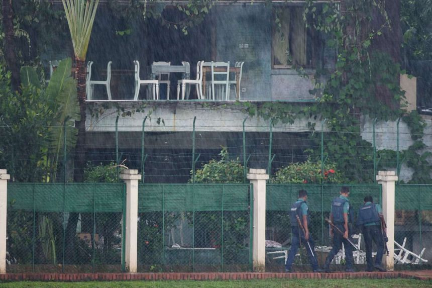 Bangladeshi policemen look into the back garden of an upscale cafe in Dhaka on July 3, 2016, a day after a bloody siege ended with the death of 20 foreign hostages.