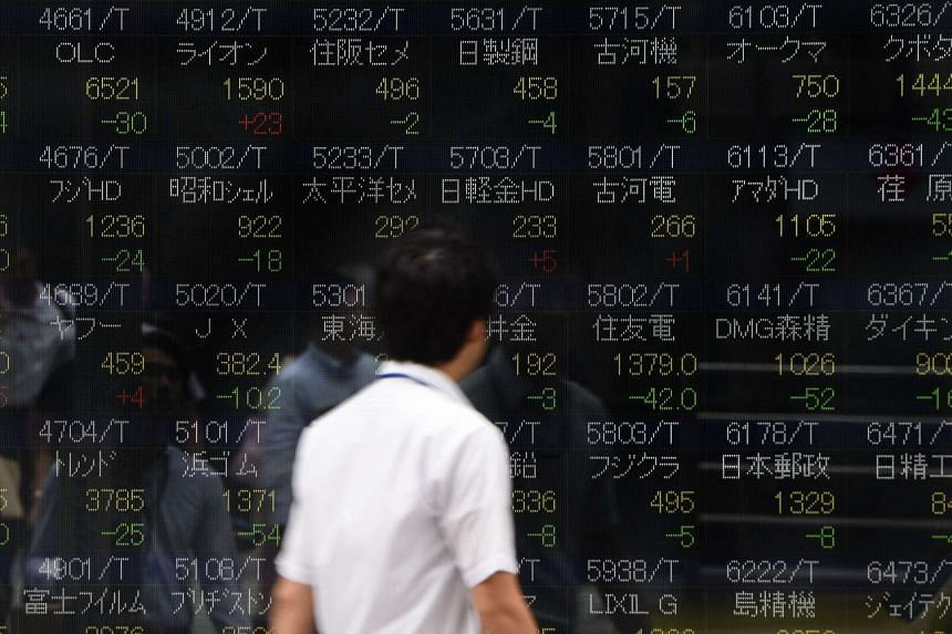 A man looks at an electric quotation board flashing share prices of the Tokyo Stock Exchange in front of a securities company in Tokyo on July 26.