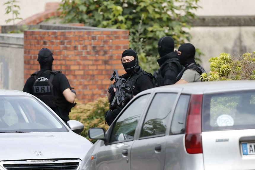 French policemen stand in the street during a search in a house on July 26, 2016, in the Normandy village of Saint-Etienne du Rouvray.