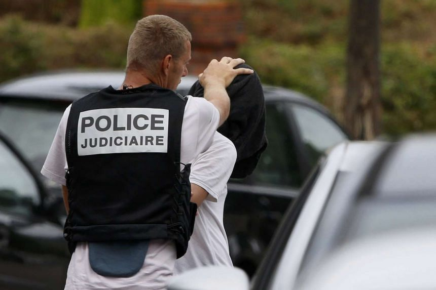 A man is apprehended during a raid after a hostage-taking in the church in Saint-Etienne-du-Rouvray.