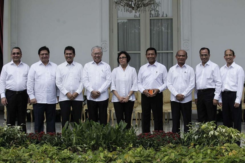 Indonesia's new cabinet ministers, including Finance Minister Sri Mulyani Indrawati (fifth from left) and  Coordinating Minister for Legal, Security and Politics Wiranto (fourth from right), pose for photos during a press conference at Merdeka Palace