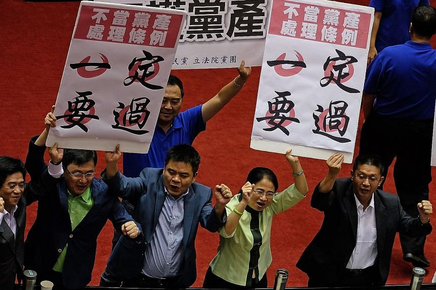 """Legislators from Taiwan's ruling DPP holding placards reading """"Ill-gotten party assets Bill must pass"""". Taiwan is set to launch an investigation into the assets of the island's political parties, a move that the opposition KMT criticised. Only the KM"""