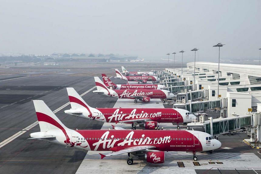 AirAsia aircraft seen next to boarding gates at Kuala Lumpur International Airport.