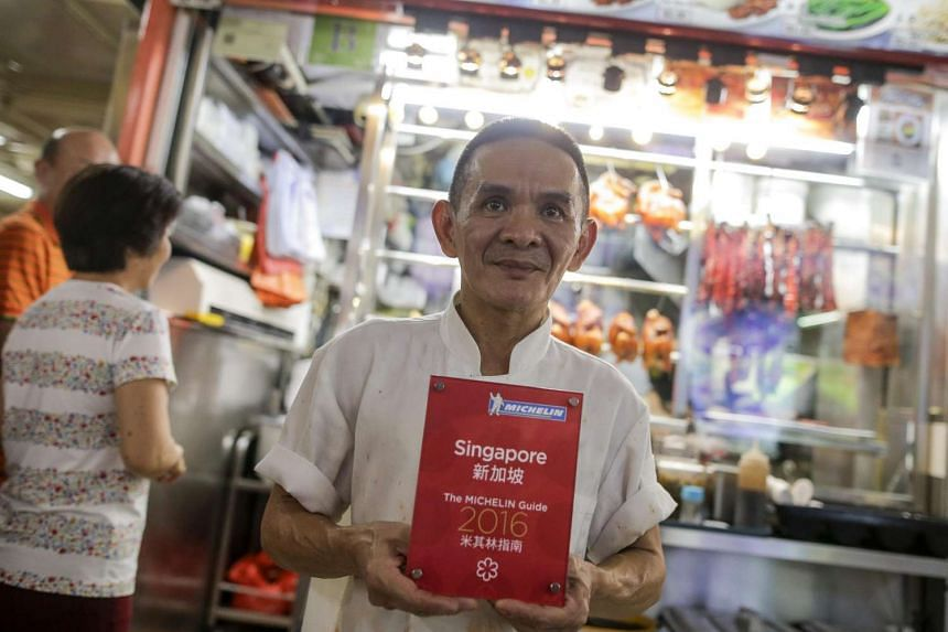 Chan Hong Meng, the owner of Hong Kong Soya Sauce Chicken Rice and Noodle, poses with his Michelin Award in front of his store in Singapore, on July 23.