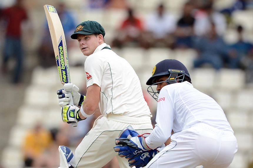 Australia's captain Steven Smith (left) plays a shot as Sri Lanka's wicketkeeper Dinesh Chandimal look on during the first day of their opening Test match between Sri Lanka and Australia.