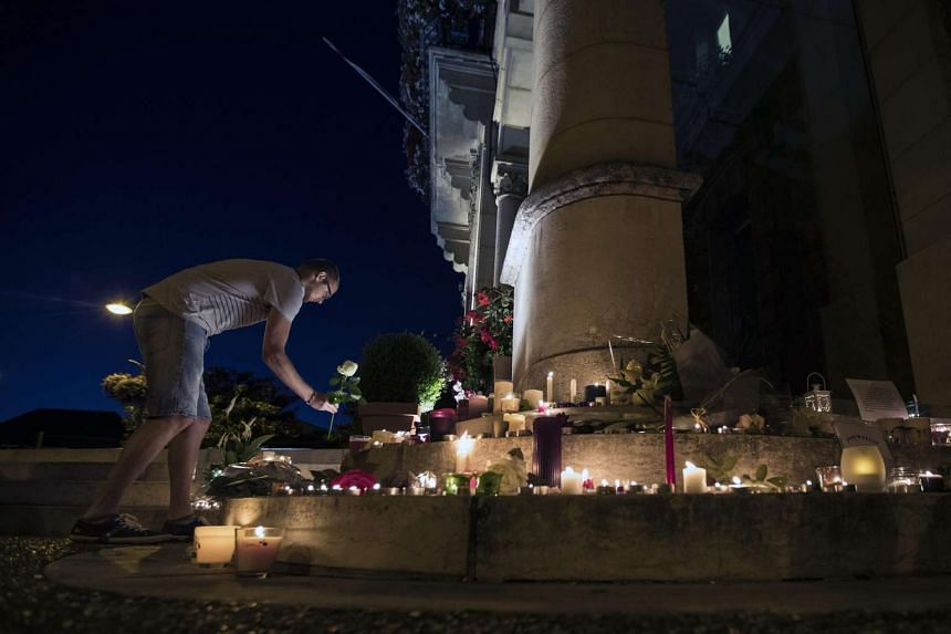 A man displays a flower at the makeshift memorial in front of the city hall after a fatal hostage taking incident at the church in Saint-Etienne-du-Rouvray, near Rouen, France, on July 26.