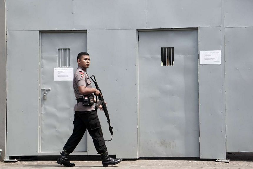 An Indonesian policeman guards outside a metal gate at the Cilacap port, the only gate to Indonesia's highest security Nusakambangan prison on July 25, 2016.