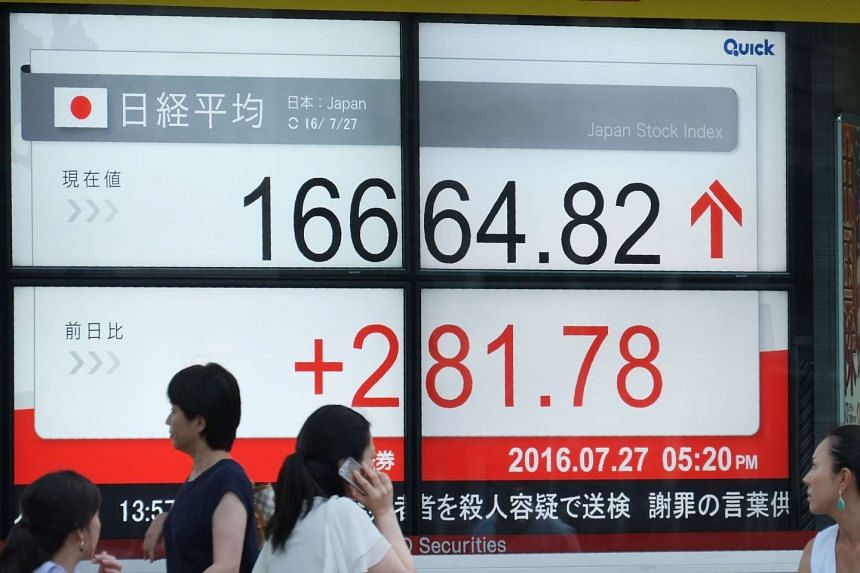 People walk past an electric quotation board displaying the Nikkei key index of the Tokyo Stock Exchange in front of a securities company in Tokyo on July 27, 2016.