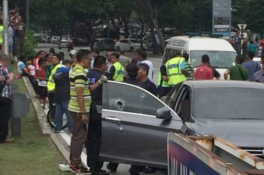 Police officers investigating the scene of a shooting near the Setapak Central mall, in Kuala Lumpur, on July 27, 2016.