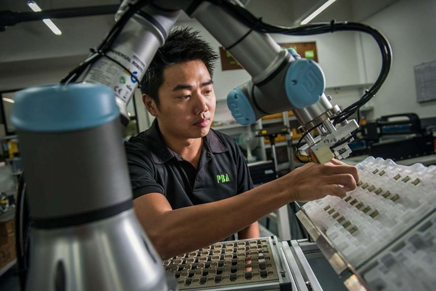 """Mr Yap arranging chips on a collaborative robot pick- and-place robotic cell. His company is now moving into robotics as factories become more """"humanless""""."""