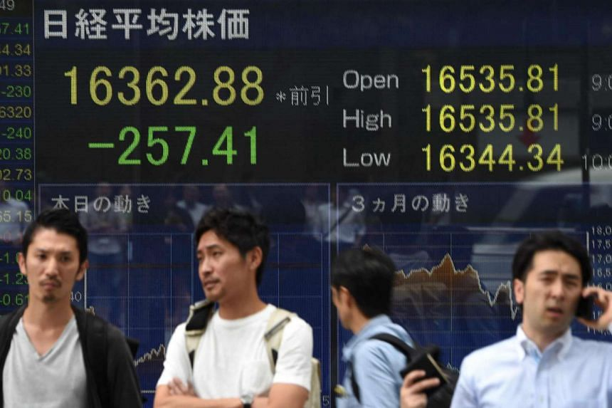 People walk past an electric quotation board flashing the Nikkei key index of the Tokyo Stock Exchange in front of a securities company in Tokyo on July 26.