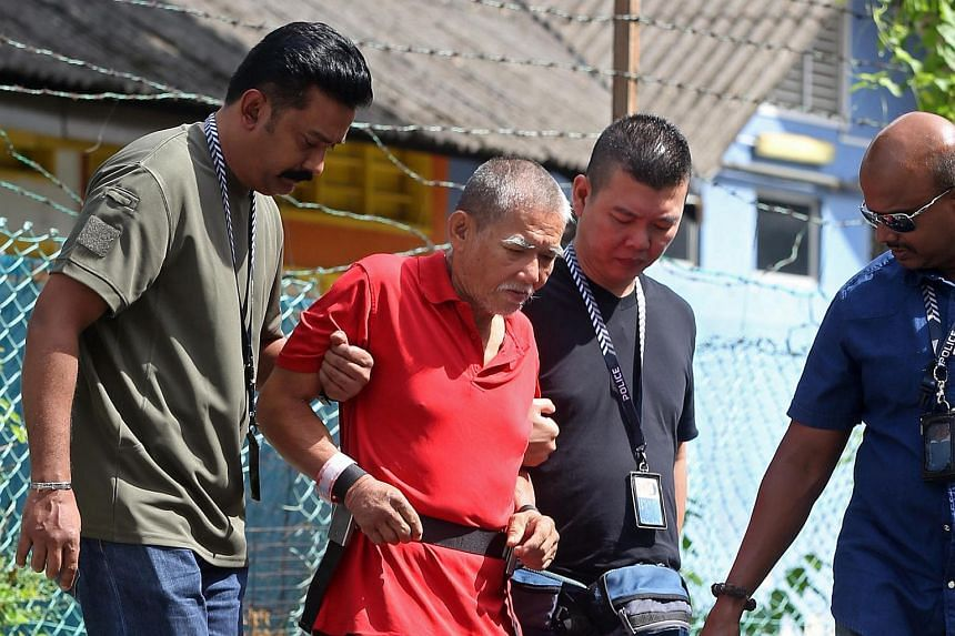 Police bringing Toh Sia Guan, 64, the suspect behind the July 9 murder of Mr Goh Eng Thiam, 52, to the scene of the crime at Geylang Lorong 23.