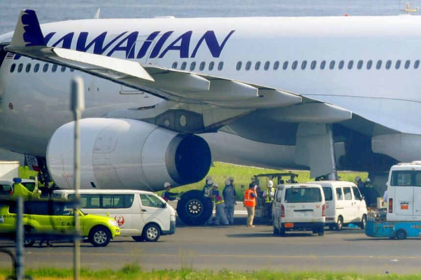 Officials change a tyre of a Hawaiian Airlines aircraft at Haneda airport in Tokyo, on July 18, 2016.