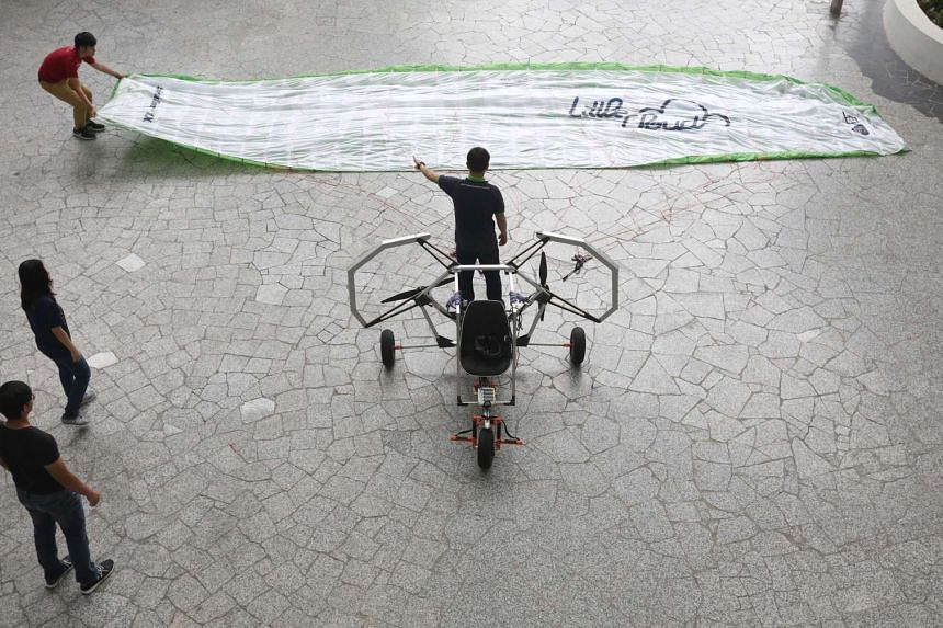 NUS engineering students adjust a banner of cloth used in a paraglider for their flying machine, The Delta.