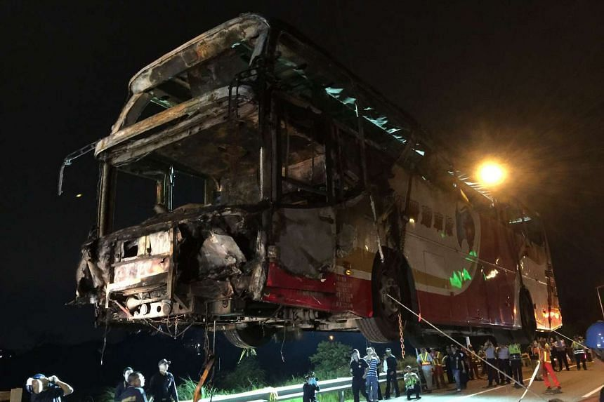 A bus is hoisted up by a crane after it earlier crashed and caught fire along an expressway on its way to the Taoyuan Airport in Taiwan, on July 19, 2016.