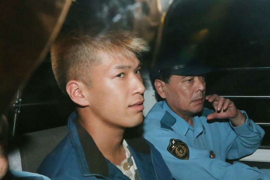 Murder suspect Satoshi Uematsu (left) sits in the back seat of a police vehicle as he returns to the Tsukui police station in Sagamihara, Kanagawa prefecture on July 27, 2016.