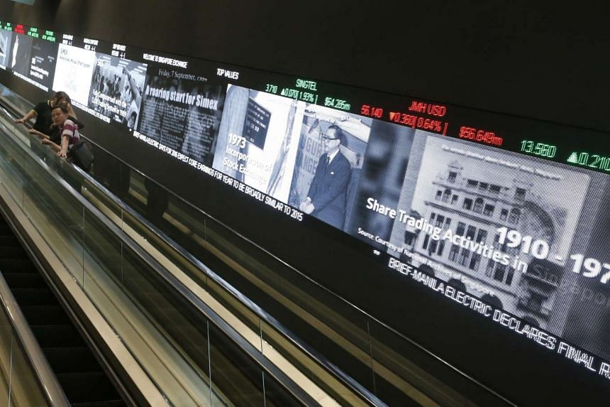 Pedestrians use an escalator that runs past an electronic screen and ticker board that indicates stock figures at the SGX headquarters on Feb 26, 2016.