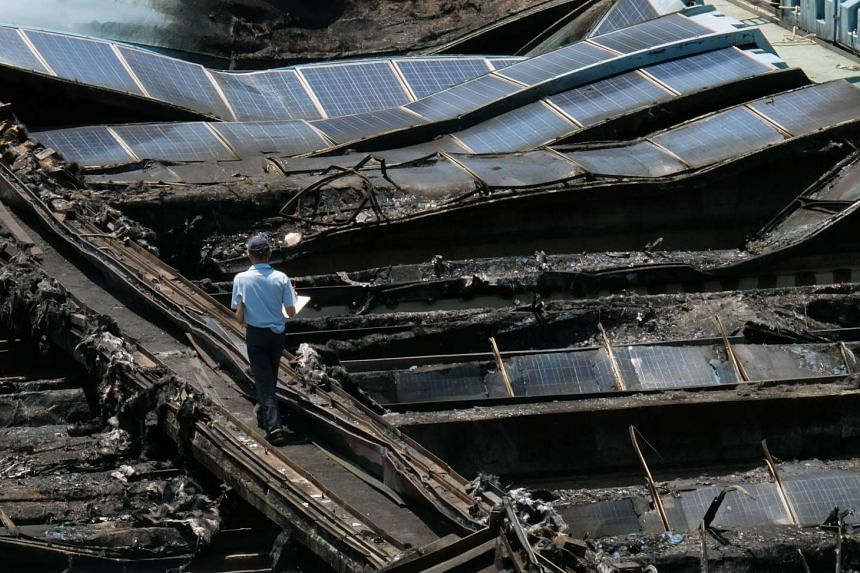 An investigator walks in the middle of burned solar panels at a Taipei water park on July 28, 2016 after they caught fire the day before.