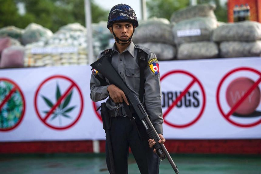 A police officer stands guard in front of seized drugs to be set on fire during a ceremony to mark the International Day against Drug Abuse and Illicit Trafficking in Yangon on June 26, 2016.