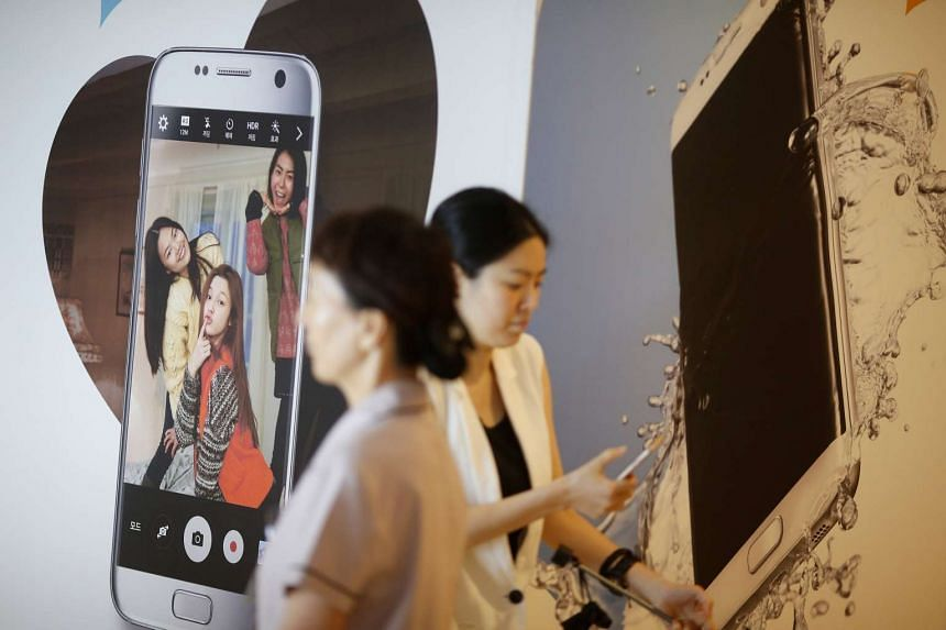 Women walk past an ad for a Samsung smartphone at the company's headquarters in South Korea.