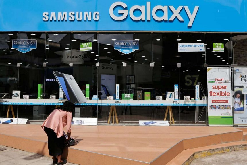 A pedestrian (left), stands outside a Samsung authorised dealer shop selling the latest Samsung products in the streets of Nairobi, Kenya on July 25.