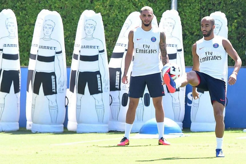 Paris Sant-Germain's Layvin Kurzawa watches as Lucas Moura juggles the ball during a training session at Loyola Marymount University in Los Angeles, California on July 26.
