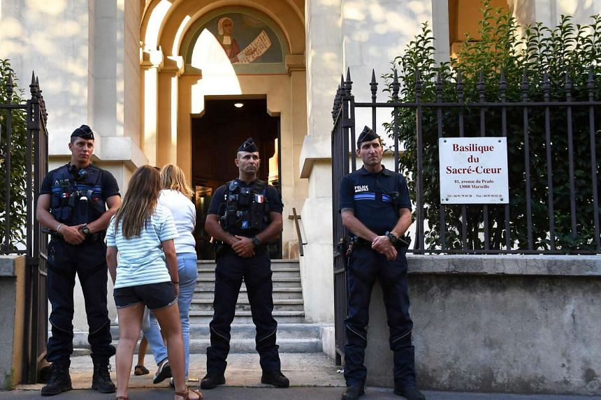 Policemen stand guard as people arrive at Sacre Coeur basilica in Marseille to attend a Mass in tribute to the priest Jacques Hamel, killed on July 26 in a church of Saint Etienne du Rouvray during a hostage-taking claimed by Islamic State group.